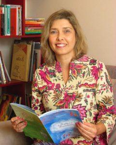 Angela Hofmann com o livro a Fada e a Fiandeira na biblioteca pessoal